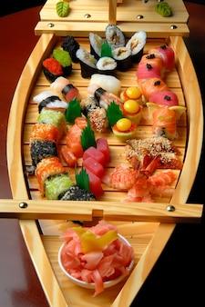 Navio com sushi e rolos em uma superfície escura