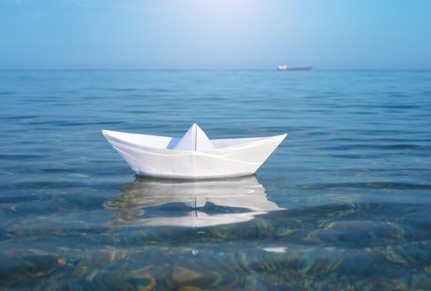 Navio de brinquedo de papel e mar azul profundo.
