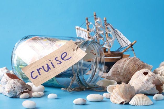 Navio de brinquedo, jarra de dinheiro e conchas do mar