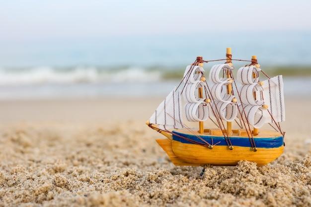 Navio de brinquedo na areia à beira-mar. conceito de férias de verão