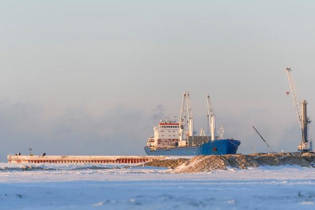 Navio de carga atracado no porto ártico. horário de inverno. navegação no gelo. carregamento em andamento