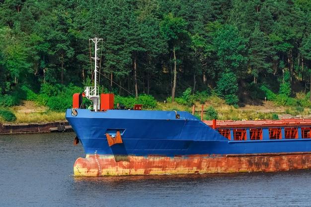 Navio de carga azul com escavadeira de longo alcance movendo-se para o porto