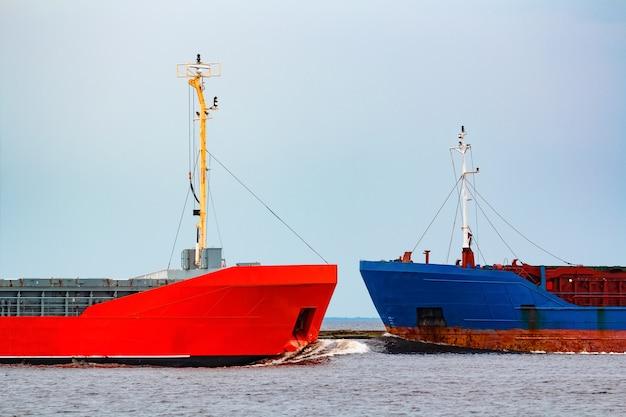 Navio de carga laranja passando pelo graneleiro azul