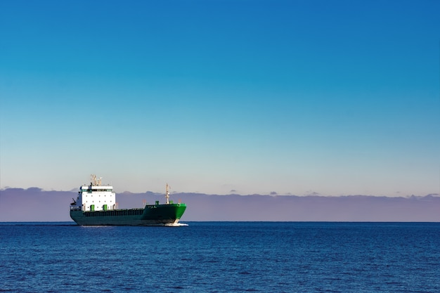 Navio de carga verde movendo-se nas águas paradas do mar báltico