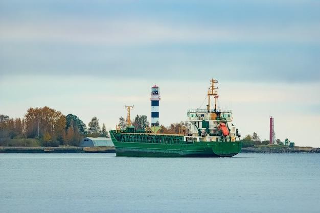 Navio de carga verde movendo-se para o porto em dia nublado