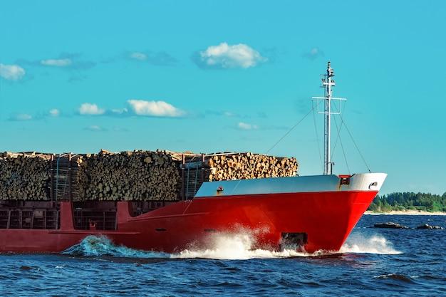 Navio de carga vermelho totalmente carregado com madeira se movendo em dia claro