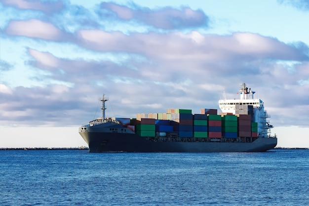 Navio de contêiner cinza moderno movendo-se em águas paradas