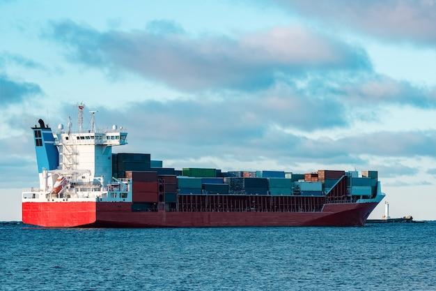 Navio de contêiner vermelho cheio movendo-se em águas paradas