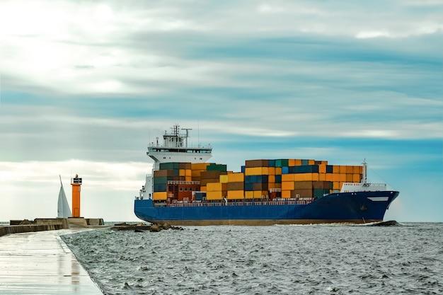 Navio de contêineres azul totalmente carregado movendo-se do mar