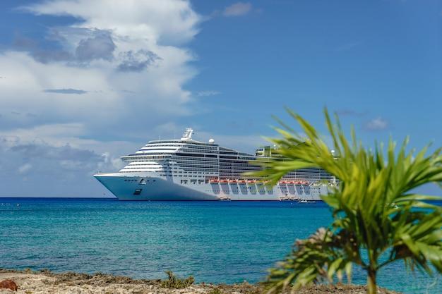 Navio de cruzeiro em águas cristalinas com uma palmeira na frente