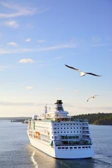 Navio de cruzeiro no mar ao pôr do sol com gaivotas voando - bela vista do mar. composição de copyspace