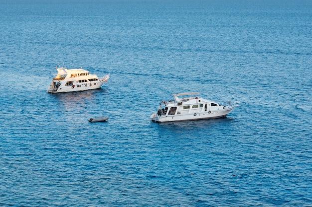 Navio de dois brancos na água azul do mar ou oceano