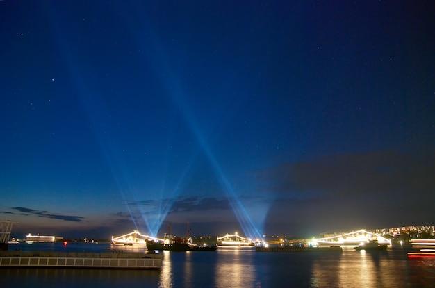 Navio de guerra iluminado e luz do feriado na baía noturna