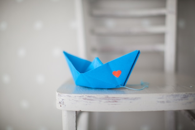 Navio de origami azul em uma cadeira