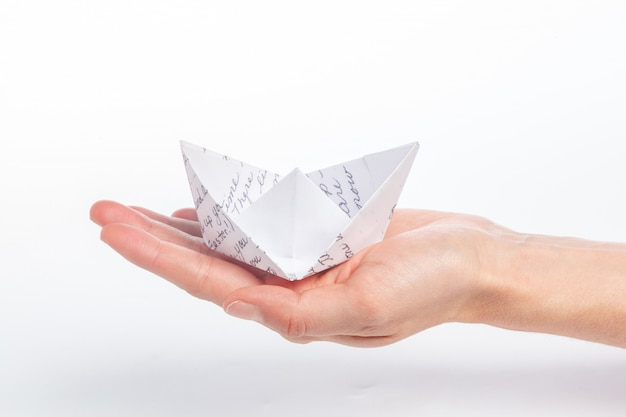 Navio de papel em uma mão feminina