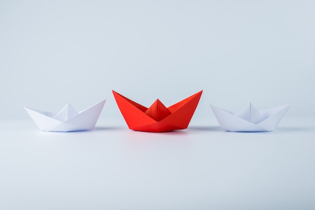 Navio de papel vermelho liderando entre branco