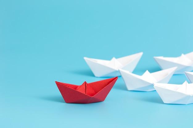 Navio de papel vermelho que conduz entre o branco no fundo azul com espaço da cópia.