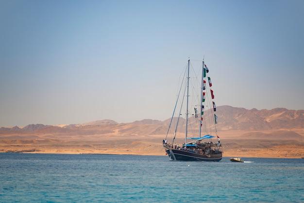 Navio do mar navegando sob a vista por do sol, sharm el sheikh, egito