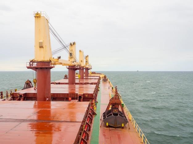 Navio graneleiro seco com guindaste caranguejo e torres com vista do convés do mar