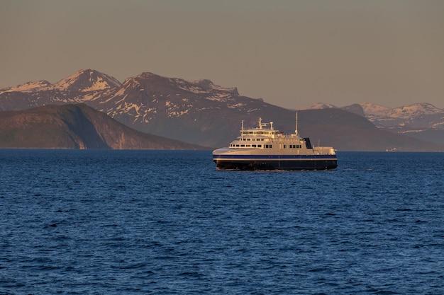Navio navegando nas águas azuis dos fiordes noruegueses no dia polar, sol da meia-noite.