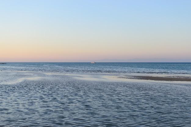 Navio no horizonte do pôr do sol do mar