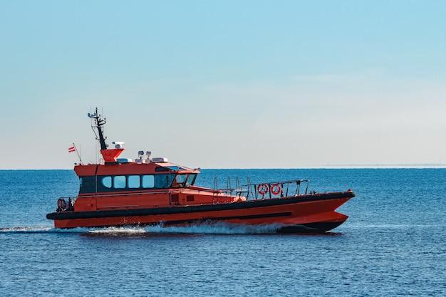 Navio-piloto laranja movendo-se rápido do mar báltico