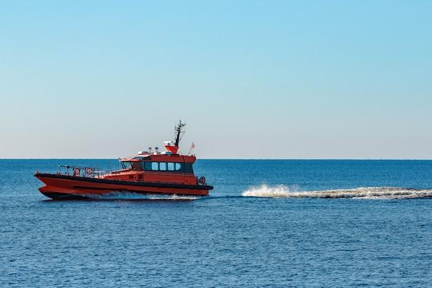 Navio-piloto laranja saindo rápido do mar báltico
