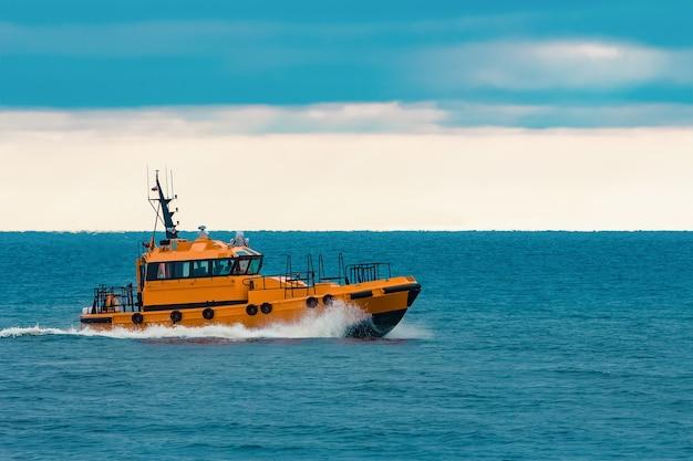 Navio-piloto laranja se movendo rápido no mar báltico