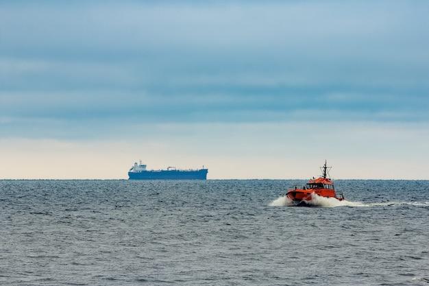 Navio-piloto vermelho movendo-se em alta velocidade no mar báltico