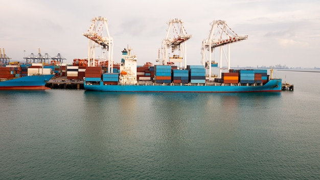Navio porta-contêineres em porto industrial na importação e exportação de serviços de negócios globais, logística e transporte, embarque de carga e descarga de navios porta-contêineres por guindastes, vista aérea