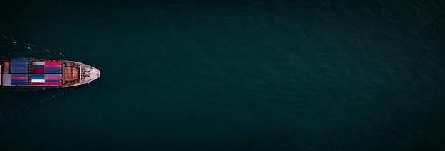 Navio porta-contêineres para importação e exportação, logística de negócios e transporte por navio porta-contêineres em mar aberto, navio de carga de contêiner de vista superior aérea com espaço de cópia para o fundo da web do banner do projeto