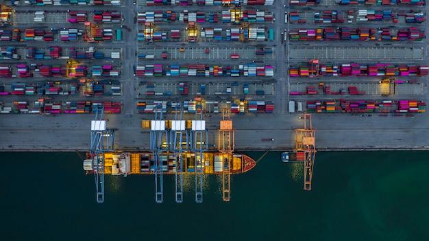 Navio porta-contentores, trabalhando à noite, negócios importação exportação logística.