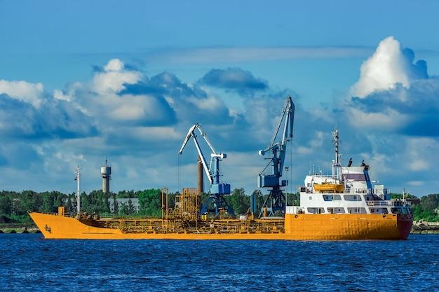 Navio-tanque de carga amarelo movendo-se em um dia claro de verão
