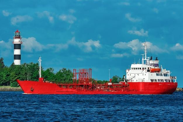 Navio-tanque de carga vermelho movendo-se perto do rio