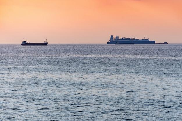 Navios de carga e barcaça ao pôr do sol