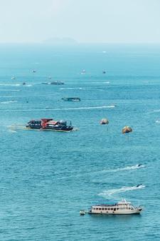 Navios que flutuam sobre o mar com o turista que joga o parasailing em pattaya, chonburi, tailândia.