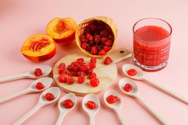 Nectarina com suco, cereja seca na mesa-de-rosa e tábua, vista de alto ângulo.