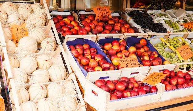 Nectarina de frutas frescas, uvas pretas e brancas, melões brancos em um mercado