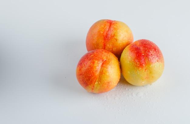 Nectarina maduras na superfície branca, vista de alto ângulo.