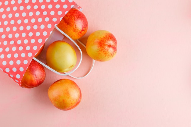 Nectarinas dispersas de um saco de papel em uma mesa rosa. configuração plana.