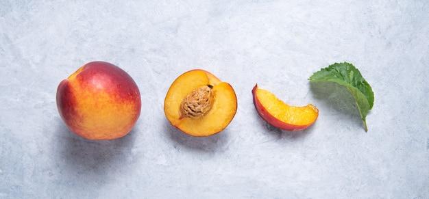 Nectarinas doces com fatias e folhas verdes sobre um fundo azul. conceito fruta plana postura. vista superior da imagem