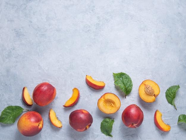 Nectarinas doces com fatias e folhas verdes sobre um fundo azul. conceito fruta plana postura. vista superior e cópia da imagem do espaço