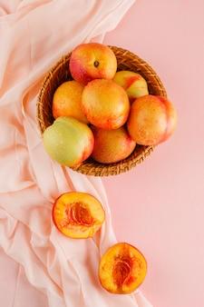 Nectarinas em uma cesta vista superior na superfície rosa e têxtil