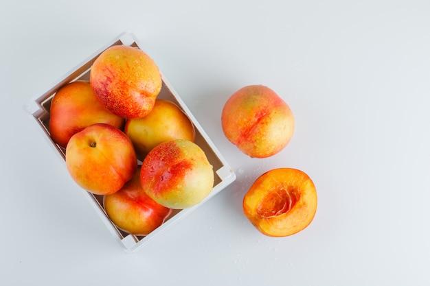 Nectarinas maduras em uma caixa de madeira na mesa branca, plana leigos.