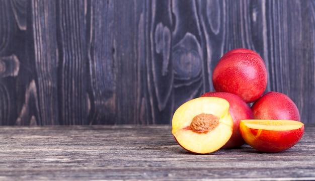 Nectarinas vermelhas suculentas, algumas das quais são cortadas em fatias, close-up da comida na mesa
