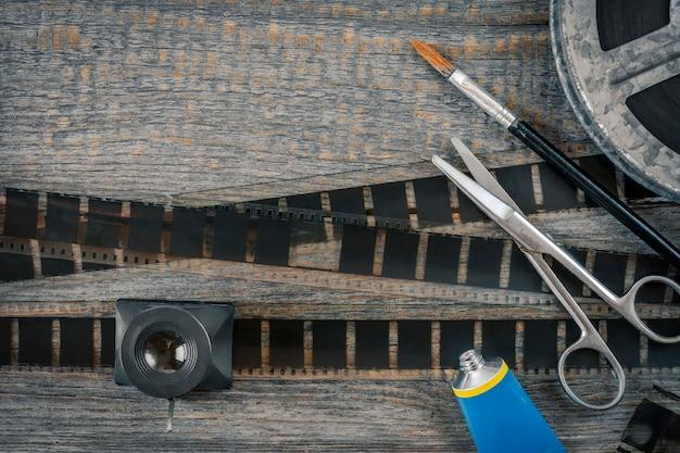 Negativos de montagem de filme, tesoura, cola e uma escova estão em uma velha mesa de madeira