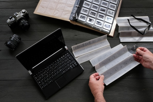 Negativos e slides fotográficos com equipamento fotográfico analógico e laptop