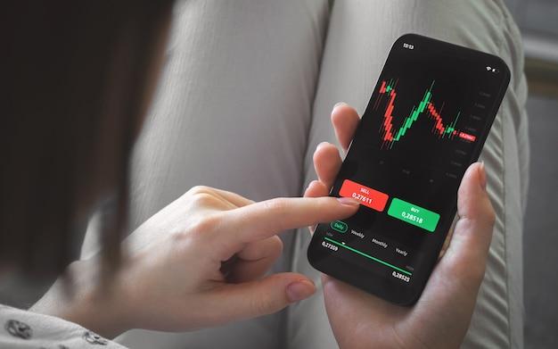 Negociação no mercado de ações em casa. telefone móvel com graps de castiçal na tela. foto do plano de fundo do conceito de investimento e análise