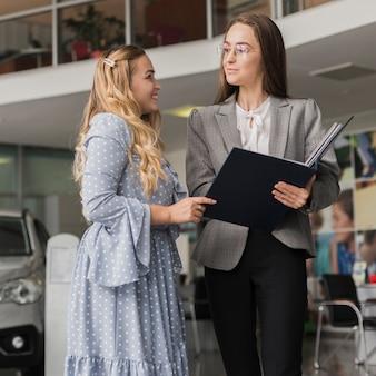 Negociante de carro conversando com mulher loira