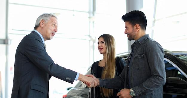 Negociante de carro dando um aperto de mão para um jovem casal